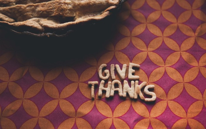 letters made from baked dough, spelling out the words give thanks, on a retro tablecloth, with an orange and purple pattern, and a pie nearby