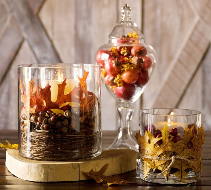 acorns and fruit, fall leaves and nuts, and lit candles, in and around three glass containers, placed on a dark brown table