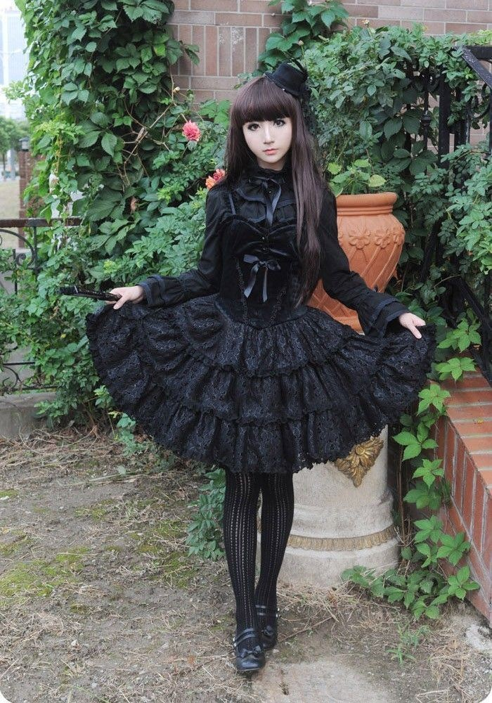 black frilly dress, with a velvet corset detail, worn by a pale girl, with long brunette hair