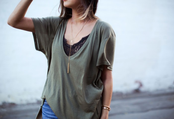 loose grayish-green v-neck t-shirt, over a black lace bralette, what to wear with a bralette, combined with blue jeans, and a long and thin gold necklace