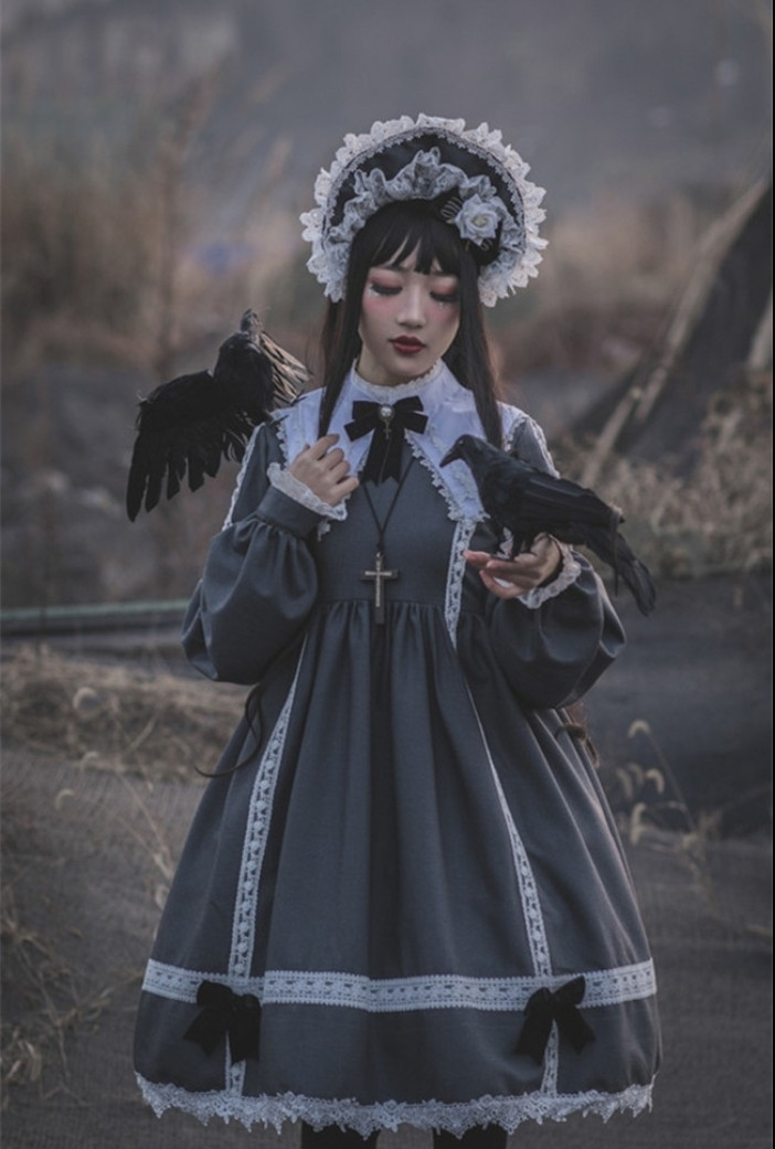 crow props held by a girl, dressed in a grey lolita outfit, with a white collar, lace details and small dark bows, frilly bonnet and a cross necklace