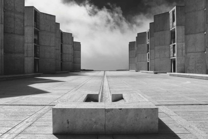 salk institute for biological sciences, in san diego california, brutalist art, courtyard covered in concrete, with angular buildings on either side