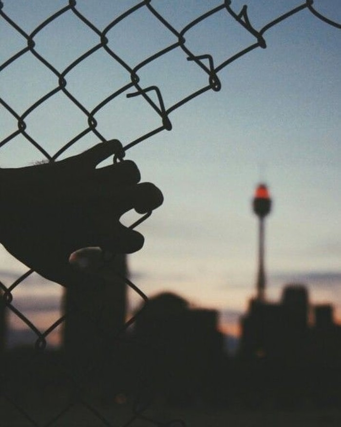 80s grunge aesthetic, hand gripping at a broken chain-link fence, overlooking a city at dusk
