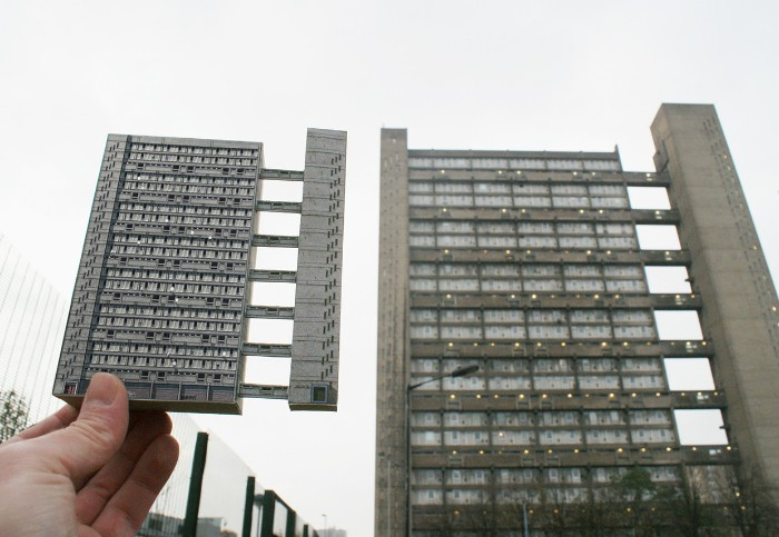 miniature model of the trellick tower, held by a hand, near the real trellic tower, concrete architecture icons