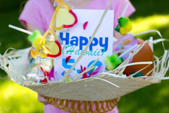 straw hat containing a card, with the inscription happy hawaii 5-0, colorful garlands and sunglasses, 50th birthday colors, held by a girl dressed in pink