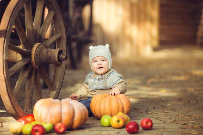 pumpkins and apples, near a sitting baby boy, dressed in a beige and light blue sweater, and dark blue jeans, baby thanksgiving outfits, pale grey hat, with small bear ears