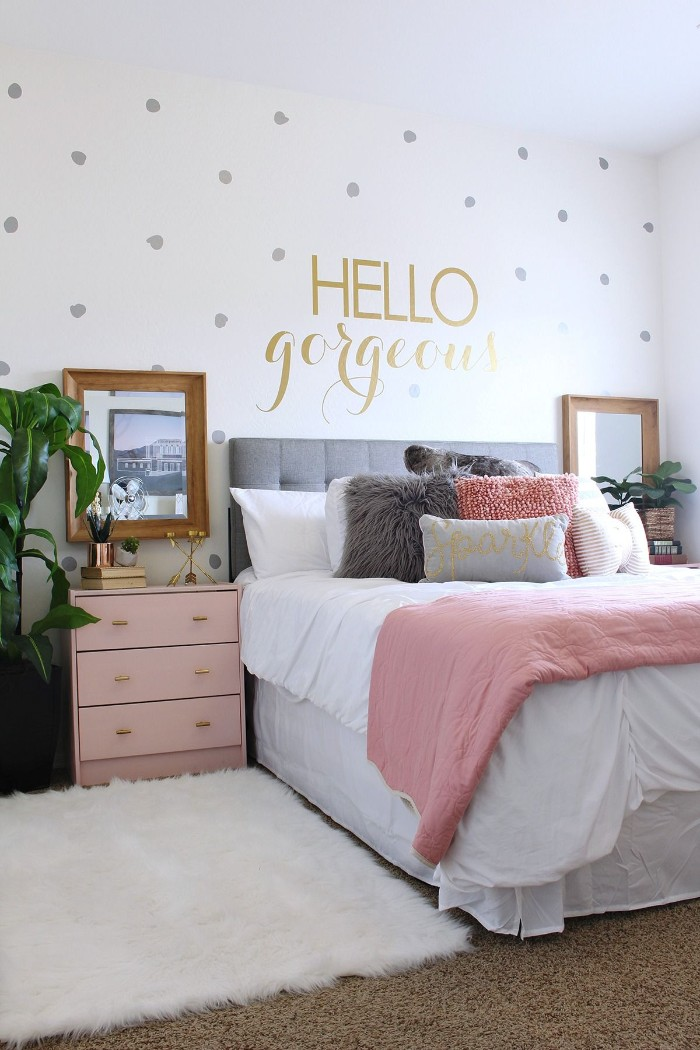 fluffy white rug, and beige carpet, in a room with white walls, decorated with silver dots, and the words hello gorgeous, written in gold, teen bedrooms, bed with several cushions, pink chest of drawers