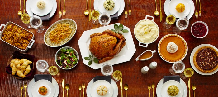 roasted turkey on a white plate, placed on a brown table, and surrounded by different dishes, pies and salads, croissants and sides, thanksgiving wishes, six sets of plates, with gold cutlery