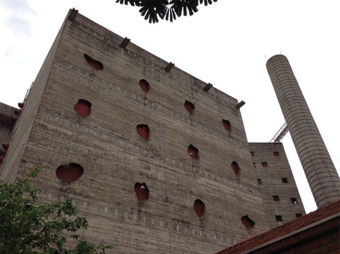 sesc pompéia in sao paulo, large brutalist design building, made of brick and concrete, featuring holes in different shapes, and a tall chimney