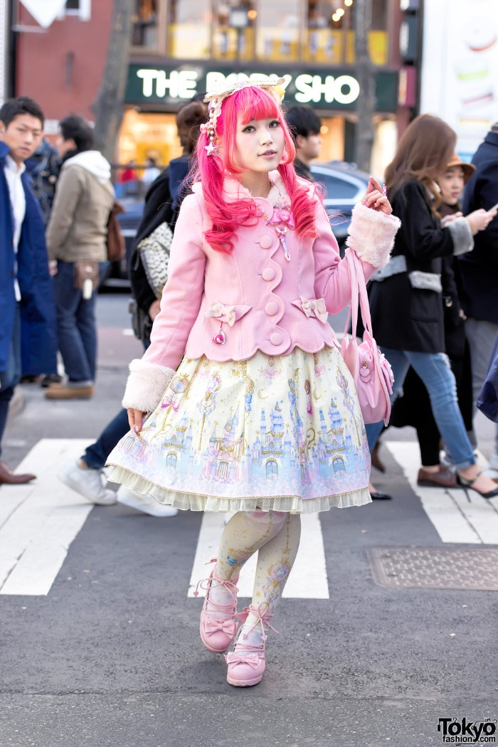 pastel pink lolita fashion coat, with faux fur trims, on a girl wearing a hot pink wig, and a cream dress with light blue motifs