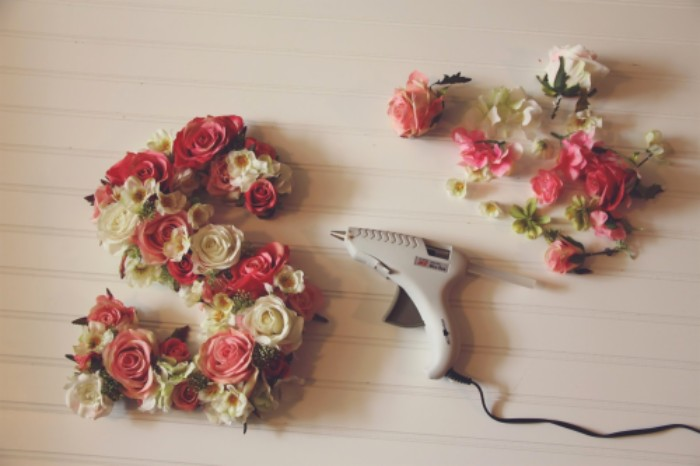 the letter s, decorated with faux roses, in pink and cream, and small fake white and yellow blossoms, teenage girl room ideas, light grey glue gun, and more fake flowers nearby