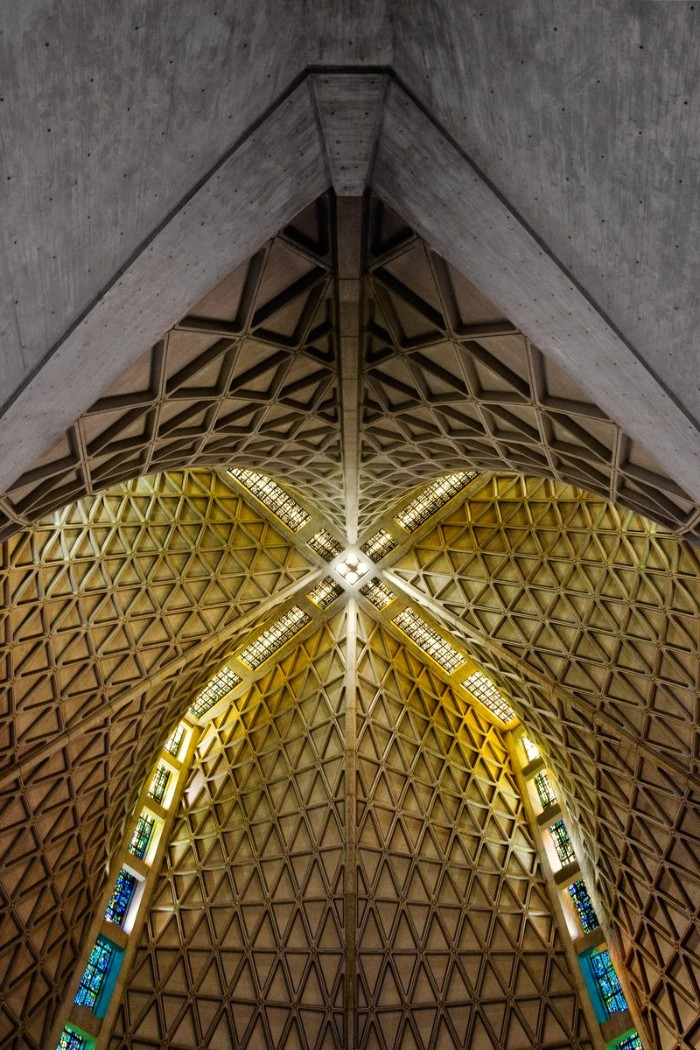 dome of a modern church, made of concrete, and seen from within, with colorful stained windows, brutalism in architecture