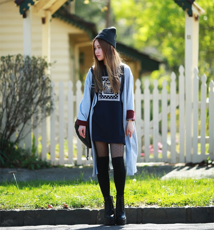 over-the-knee socks in black, worn with sheer black patterned tights, a dark grey jumper mini dress, black combat boots, and an oversized pale blue cardigan, 90s grunge fashion, on a slim young woman, with long brunette hair, and a grey beanie hat