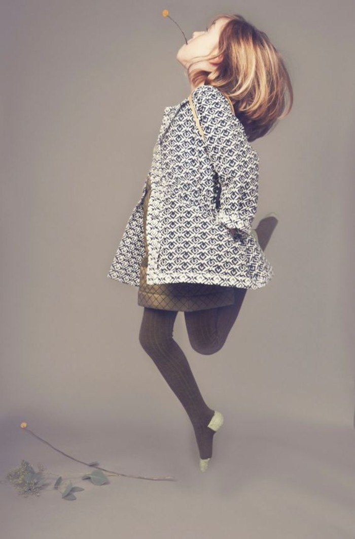 little girl with shoulder-length blonde hair, and a yellow flower in her mouth, jumping in the air, dressed in a white and black patterned coat, a khaki short dress, and dark grey knitted tights, girls thanksgiving outfit