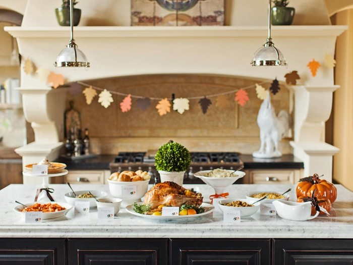 paper garland featuring fall leaves, in different colors, hanging near an antique-style stove, thanksgiving wishes, kitchen island covered in different dishes and foods