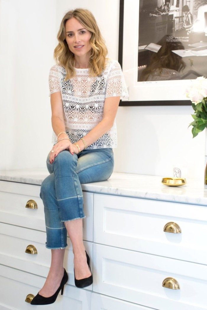 woman sitting on a cupboard, dressed in blue ankle jeans, a see-through embroidered t-shirt in white, and a black bralette, outfits with bralettes, black high heel shoes