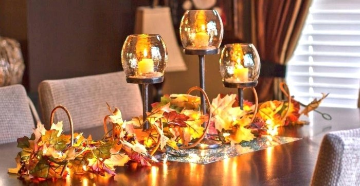 candle holders made of glass and metal, each containing a lit, small yellow candle, on a dark brown table, decorated with orange and yellow, faux fall leaves