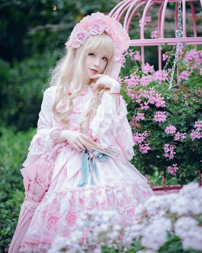 garden with pink blossoms, behind a girl in a blonde wig, wearing a white frilly dress, decorated with a subtle rose pattern, she holds a fan and a pink parasol