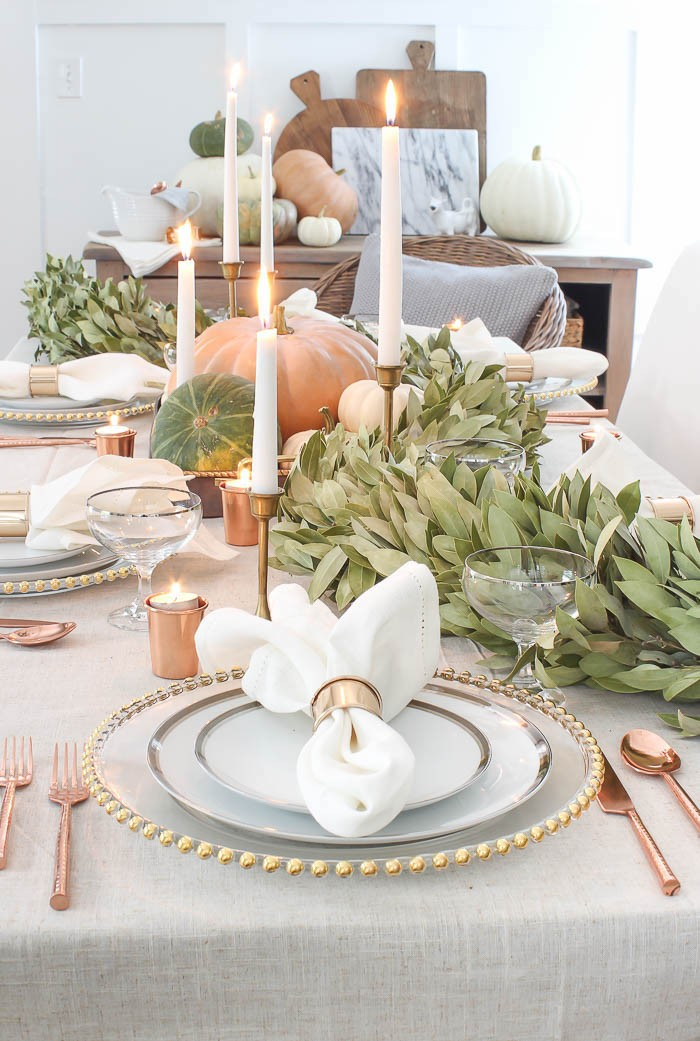 rose gold cutlery, placed near three stacked plates, with gold and silver details, thanksgiving table decorations, lit candles and several pumpkins, green decorative plants