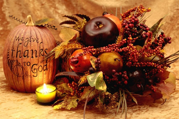 we give thanks to god, carved on a faux pumpkin, placed near a small lit candle, and a fall-themed decorative arrangement