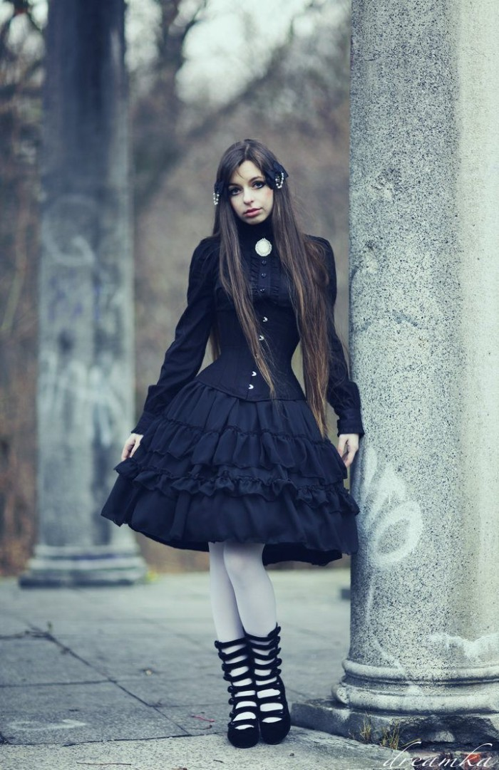 long brunette hair, on a pale girl, wearing a black frilly dress, with a black corset, and white tights, define lolita, black shoes with multiple straps, and a cameo brooch