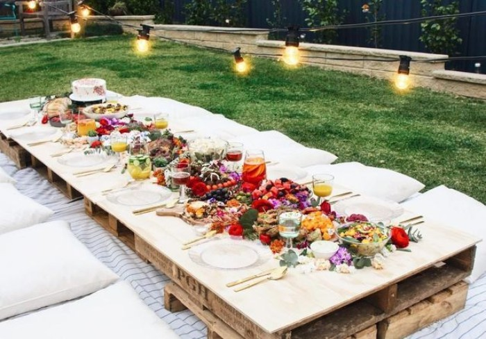 pallets used to make a table, set up for a festive meal, and decorated with a variety of flowers, 50th birthday party ideas for mom, boho garden picnic, with string lights overhead