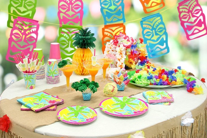 50th birthday colors, hawaiian-themed party, with colorful tiki-mask garlands, and a table decorated with a paper pineapple, multicolored plates and orange cocktails