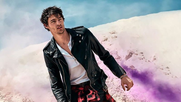 biker jacket made from glossy black leather, worn over a white shirt, by a man with messy short black hair and stubble, with a plaid shirt around his waist, 90s bands inspired attire