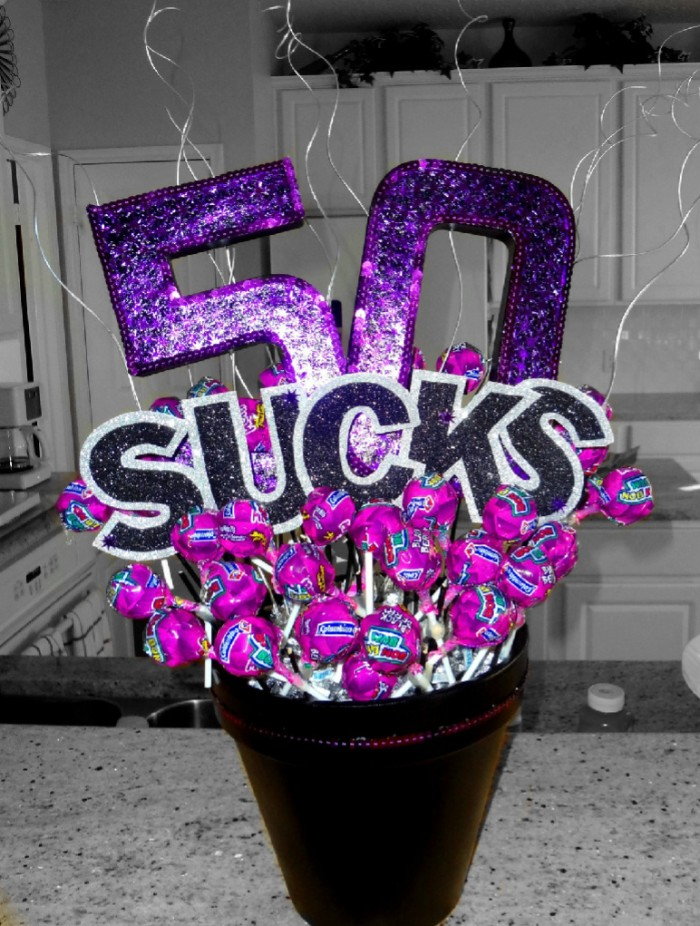 glittering purple decoration, reading 50 sucks, placed in a small bucket, filled with lolipops, in purple wrappers
