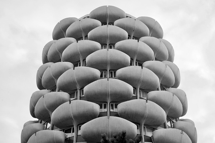 pod-like terraces made from grey concrete, attached to a tall building, types of brutalism, black and white image