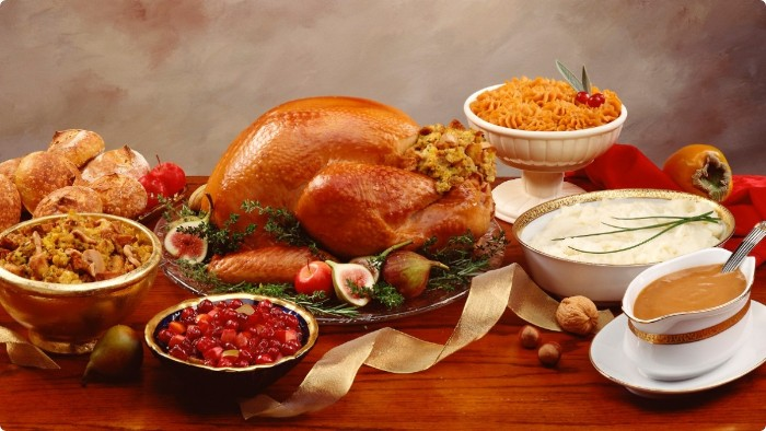 bread rolls and mashed potato, roasted turkey and several side dishes, thanksgiving greeting message, rustic wooden table