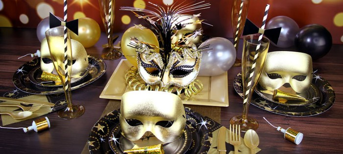 four venetain-style masks, in metallic gold, three plain and one decorated with flowers and glitter, on a table set for a party, 50th birthday ideas, masked ball theme