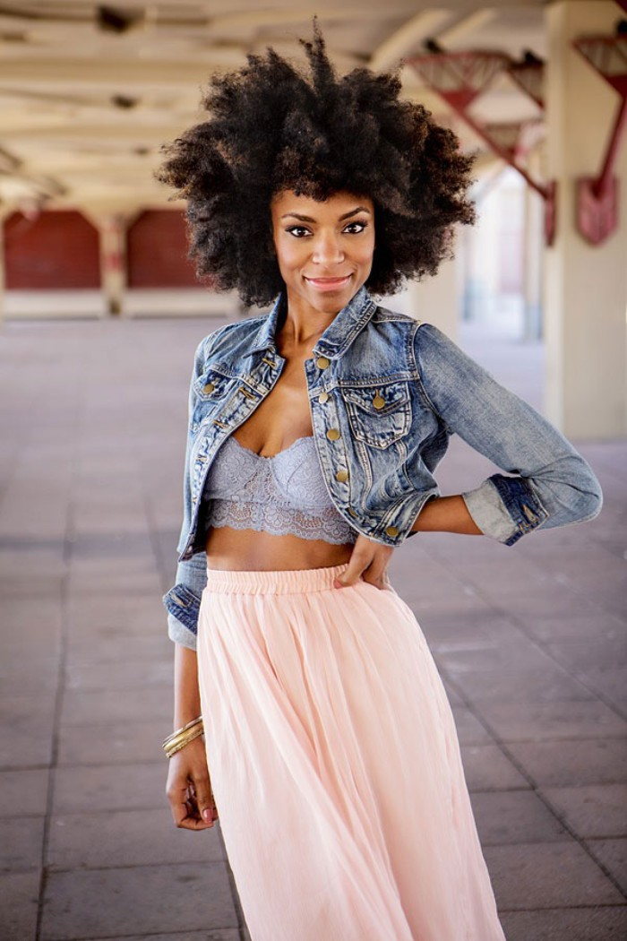 how to wear a bralette, smiling black woman, with an afro hairstyle, dressed in a pale pink maxi skirt, a light blue lace bralette, and a cropped denim jacket