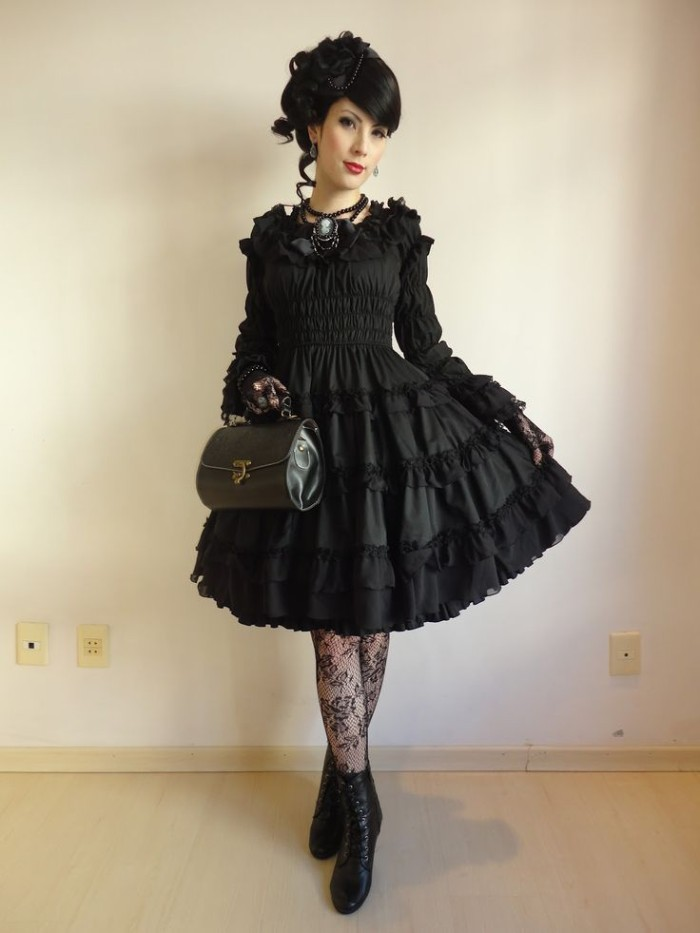frilly black dress, with lace trims, worn over black, meshy sheer tights, with floral shapes, define lolita, on a young woman with black hair, and red lipstick