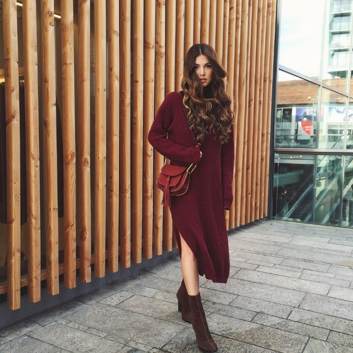 wine jumper dress, with a side slit, worn with dark brown sueded boots, and a brown leather bag, thanksgiving outfits, brunette woman with long curled hair