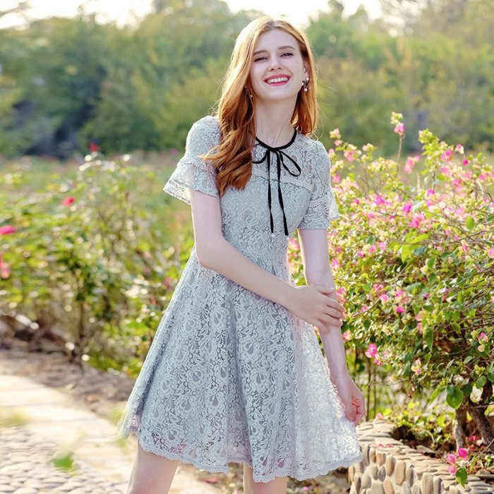 laughing slim young woman, with wavy ginger hair, wearing an off-white lace mini dress, with a black ribbon, what is lolita