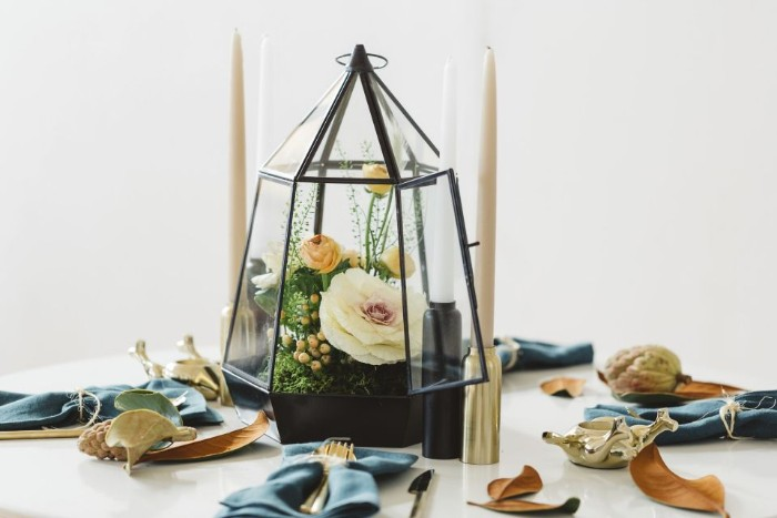 terrarium made of glass, with black frames, containing a white flower, and several yellow blossoms, thanksgiving table decorations, on a round white table, sprinkled with fall leaves