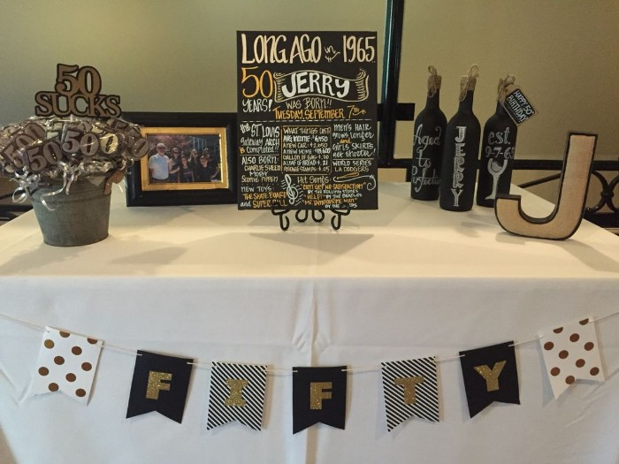 simple birthday decor, table with a festive poster, three hand-painted wine bottles, a bucket with lollies shaped like the number 50, a j-shaped decoration, and a family photo in a frame