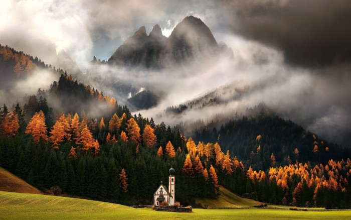 peak of a tall mountain, surrounded by white mist, happy thanksgiving wishes, hills covered in dark green, and bright orange trees, pale green meadow with a church