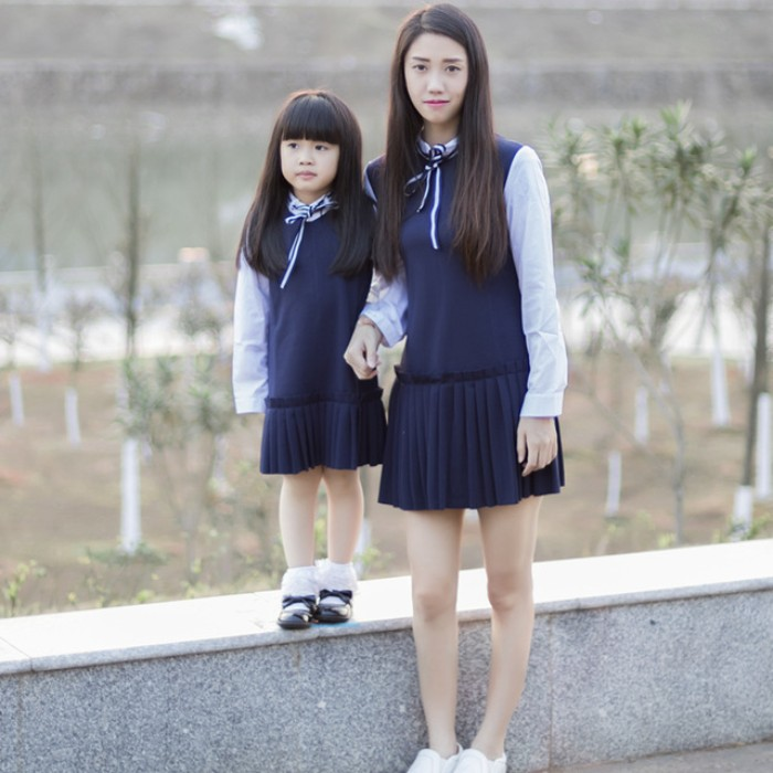mother and small daughter, wearing the same sleeveless, navy blue dresses, with pleated skirts, over white shirts, with striped blue and white ribbon ties, cute thanksgiving outfits for kids