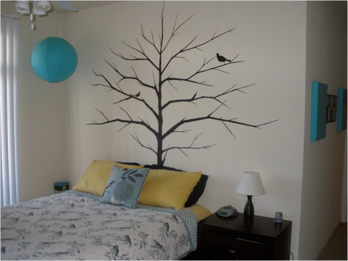 tree with bare branches, and two birds, painted in black, on a pale cream wall, cute teen rooms, bed and a dark brown cupboard