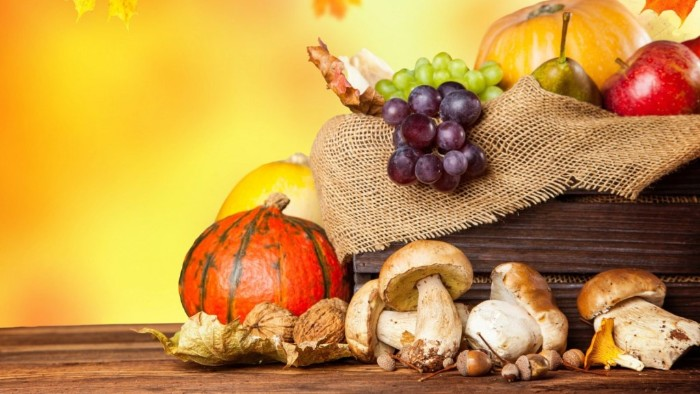 grapes and pears, apples and pumpkins, and several mushrooms, inside and next to a wooden crate, lined with burlap, thanksgiving card messages