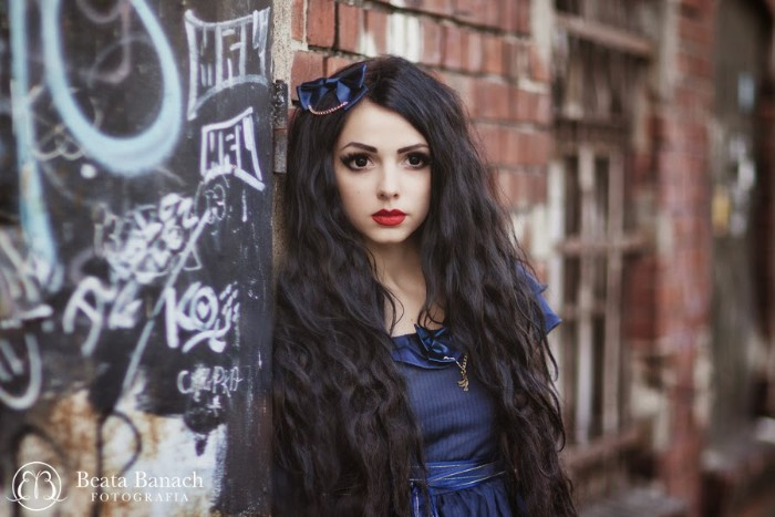 lipstick in red and black eyeliner, on a pale young woman, wearing a blue dress, and a matching blue bow in her hair