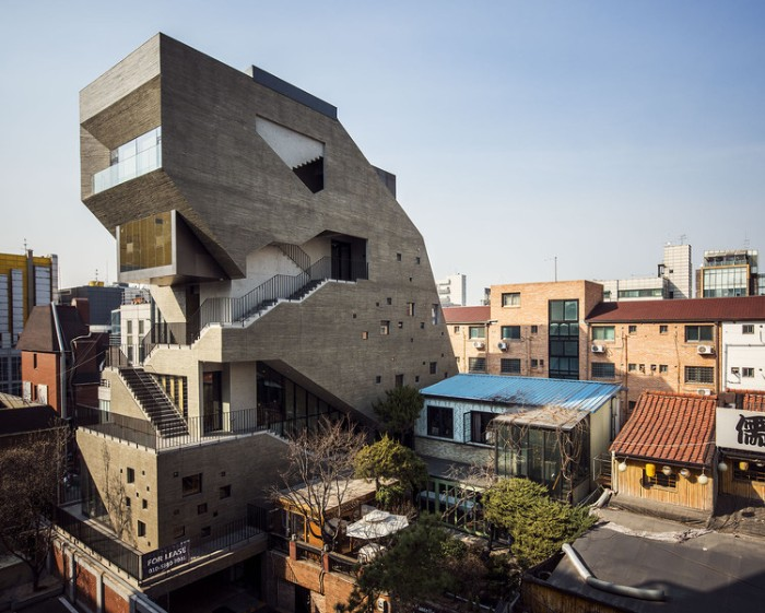 tall assymetrical building, with multiple staircases, terraces and windows in different sizes, concrete architecture around the globe