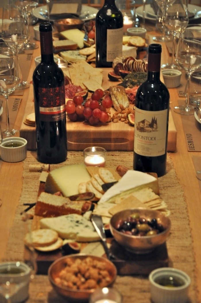 olives and nuts, grapes and cheese, on a table with three wine bottles, and small lit candles, 50th birthday themes, wine tasting party