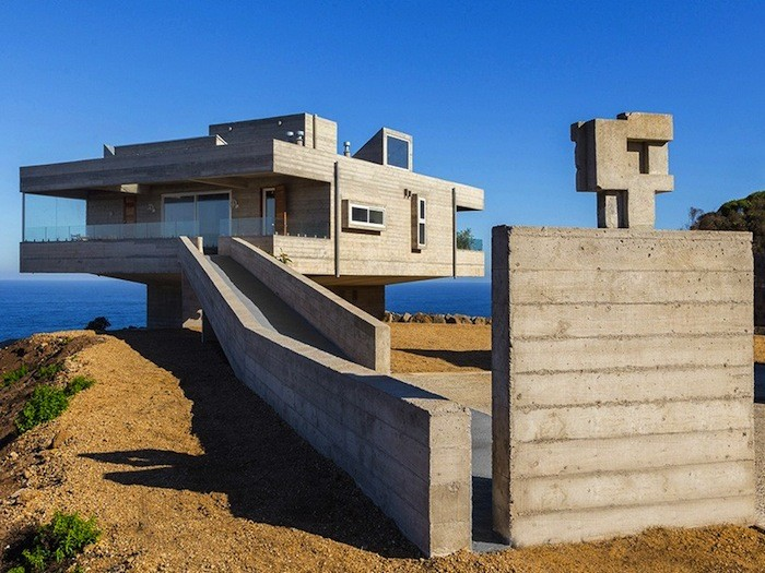 private house in valparaiso chile, situated on a beach, near the sea, and made of pale grey concrete