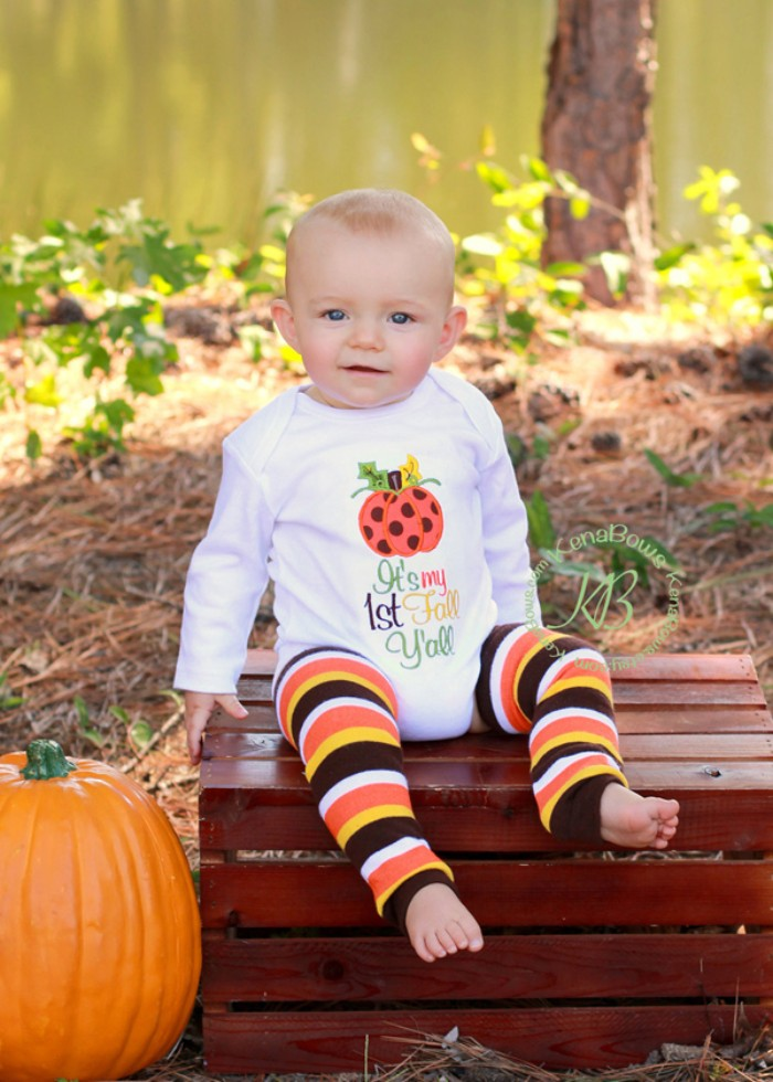 infant wearing a white onesie, with long sleeves, and a multicolored festive print, baby's first thanksgiving outfit, striped leggings in brown and yellow, white and orange