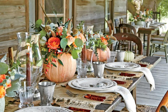outdoor wooden tables, decorated with pumpkins, filled with flowers, thanksgiving dinnerware, lit candles in glass vases, white dishes and napkins