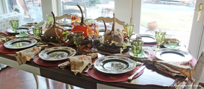 set table with eight plates, eight clear green wine glasses, floral napkins and silver cutlery, and a centerpiece, featuring several wrapped pumpkins, near a several windows