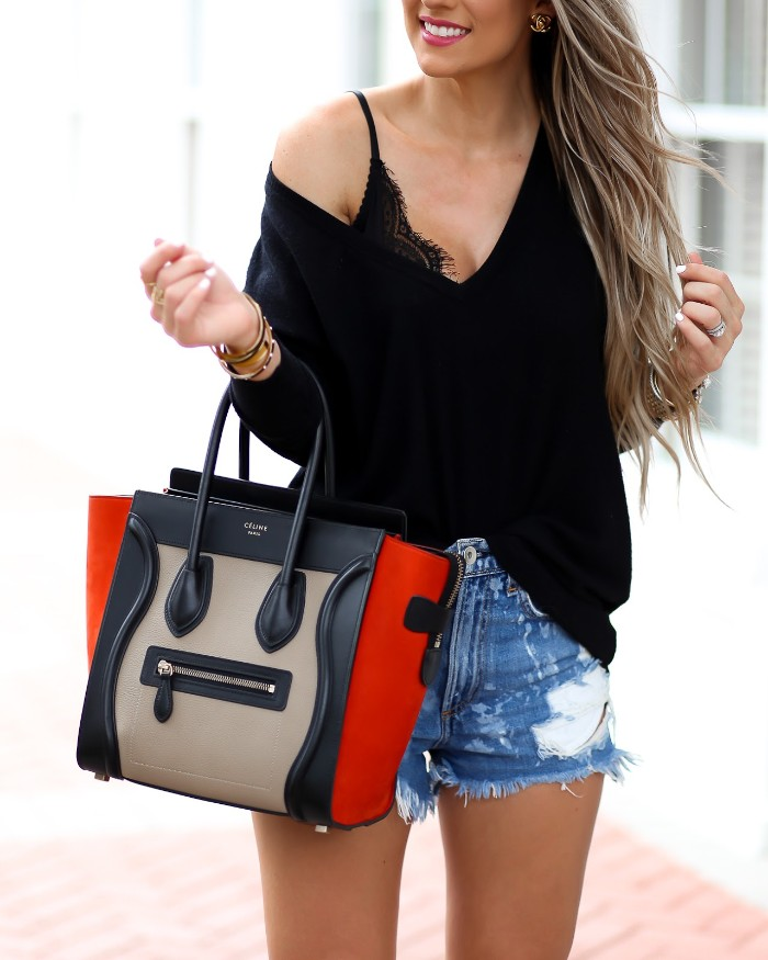 bag in black, beige and red, held by a slim young woman, dressed in distressed, blue denim cutoff shorts, a black lace bralette, and a baggy black v-neck jumper, bralette outfit, long wavy blonde hair